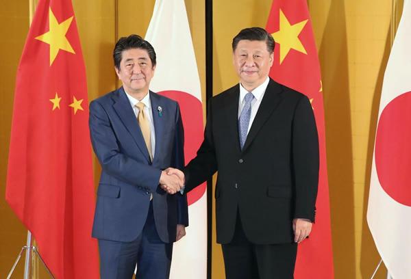 中国の習近平国家主席(右)と握手する安倍首相