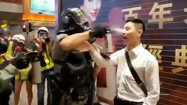 至近距離からスプレーを噴射する香港の武装警官
