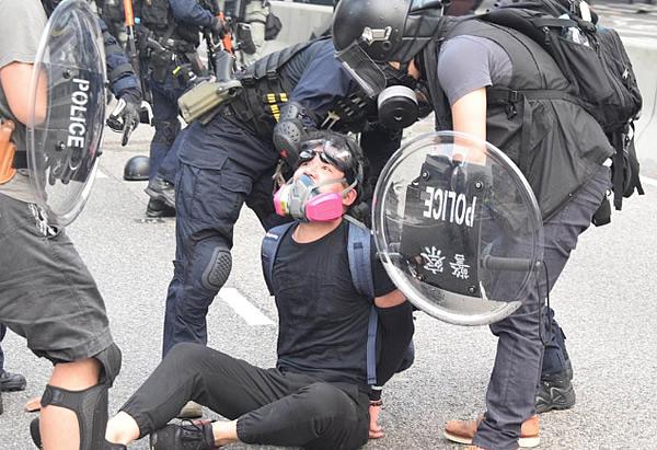 警察に拘束されるデモに参加した若者