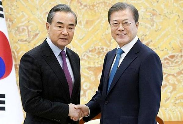 ソウルの大統領府で握手する韓国の文在寅大統領(右)と中国の王毅国務委員兼外相