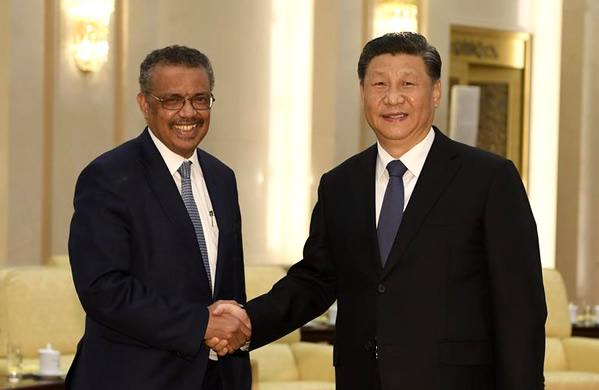 握手する中国の習近平国家主席(右)と、世界保健機関(WHO)のテドロス事務局長
