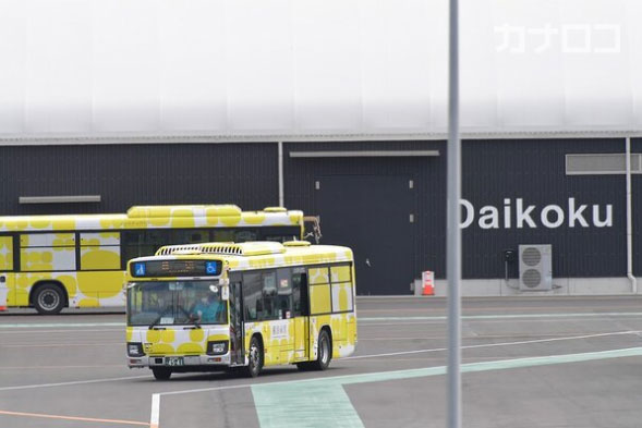 下船した人たちを乗せたとみられ、動き出すバス=19日午前11時10分ごろ、横浜港・大黒ふ頭