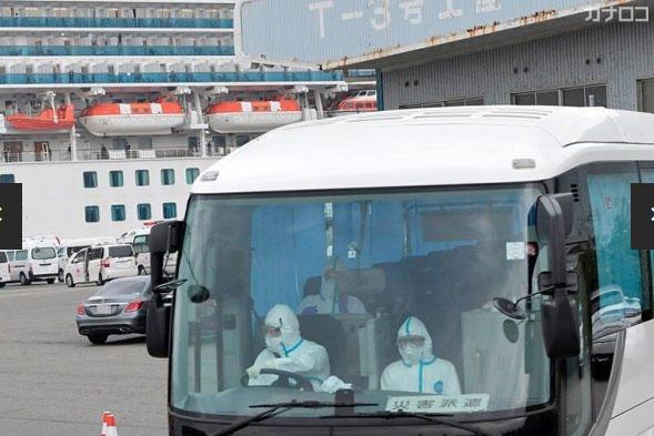 クルーズ船「ダイヤモンド・プリンセス」から出発するバス。陰性が確認された80歳以上の希望者の下船が始まった=14日午後2時55分ごろ、横浜港・大黒ふ頭