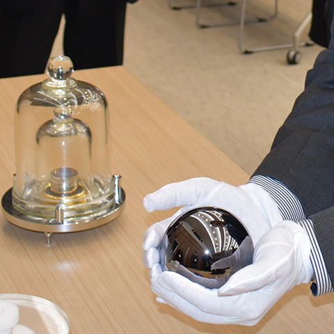 新しいキログラム定義のためのシリコン球(手前)と「日本国キログラム原器」。ともにレプリカ