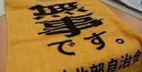 無事ですと書かれた黄色いタオル