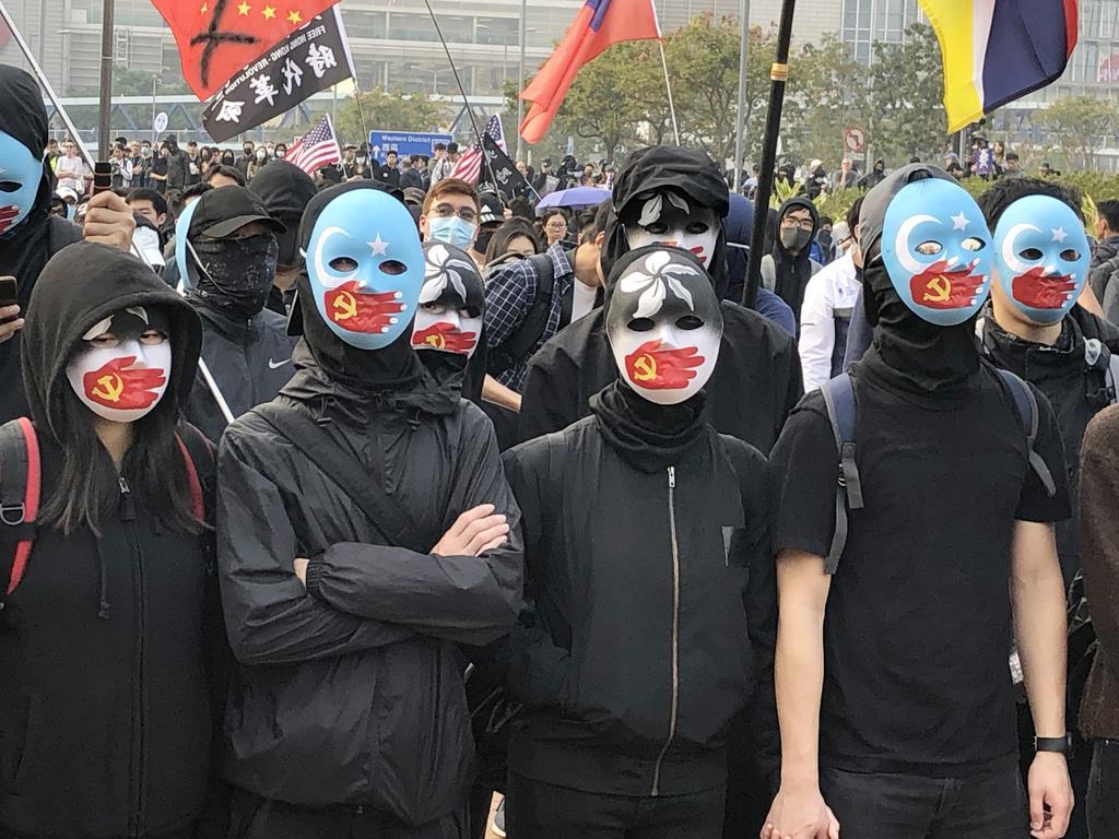 wor1912220009-p3_中国当局の少数民族ウイグル族への人権侵害を非難する集会に参加する人ら=22日、香港(共同)